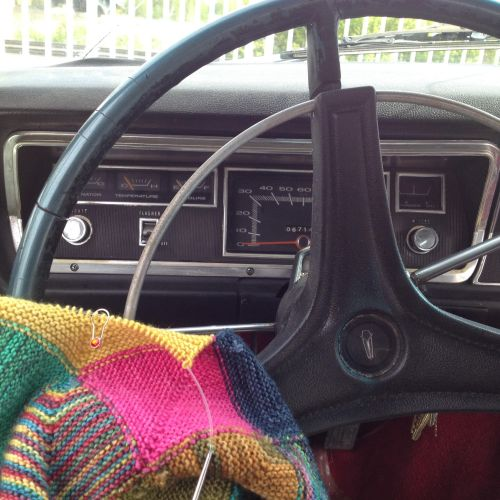 Knitting in the car in a road trip while having some minor mechanical difficulties. My spouse is working on the brakes, and I'm helping bleed them while knitting! You can knit anywhere!